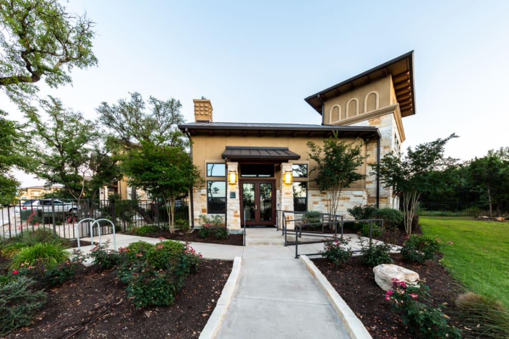 Well manicured clubhouse entrance lined with flowers and plants at Marquis at Barton Trails in Austin, Texas