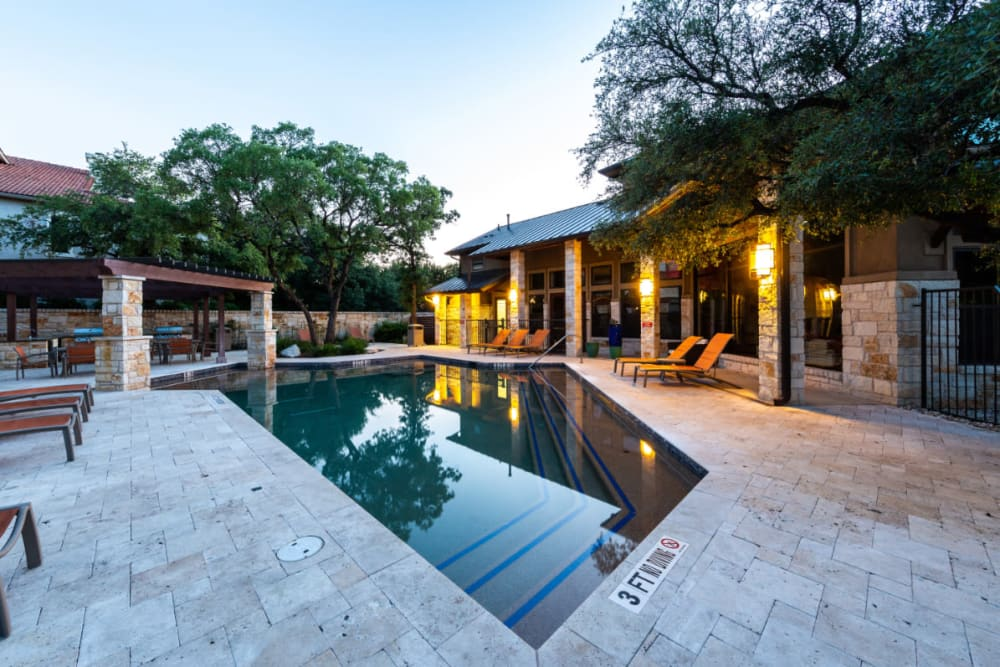 Pool area with lounge chairs at sunset at Marquis at Barton Trails in Austin, Texas