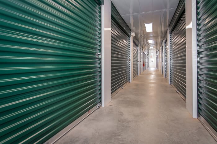 Well lit indoor hallway of storage units at Space Shop Self Storage in Greenville, South Carolina