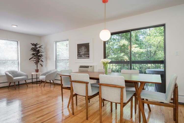 Well-lit model dining room featuring extravagant wooden flooring at Everly Roseland in Roseland, New Jersey