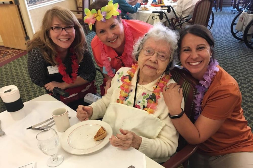 Female resident enjoying Hawaiian theme day with female staff members at St. Andrews Health Campus in Batesville, Indiana