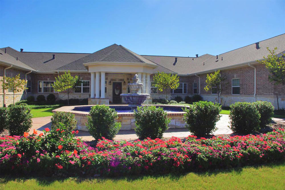 Garden and patio with a fountain at The Village at Silver Sage in Haltom City, Texas