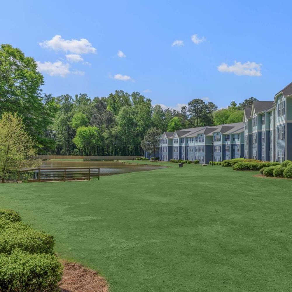 Expansive and beautifully maintained lawn between the lake and resident buildings at The Bentley at Marietta in Marietta, Georgia