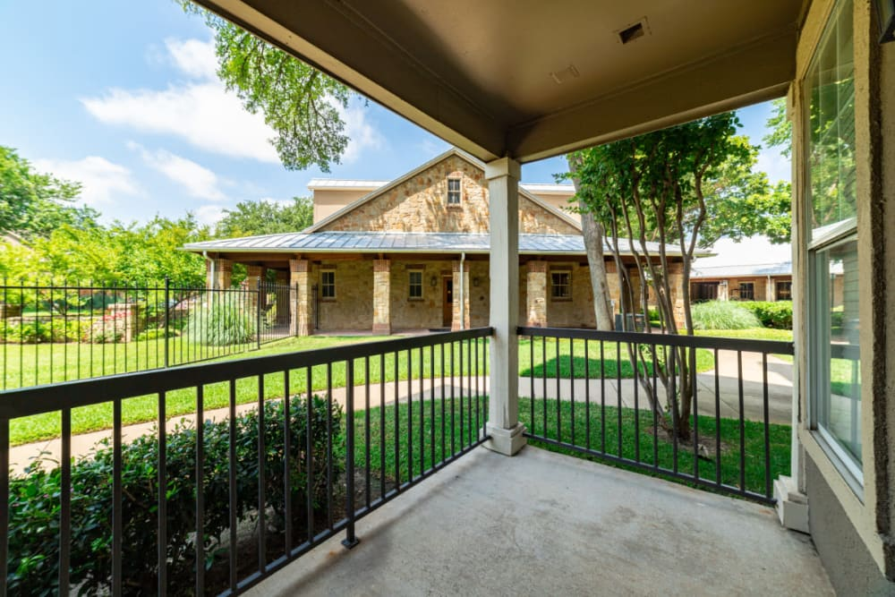 Private balcony surrounded by green grass and trees at Marquis at Bellaire Ranch in Fort Worth, Texas
