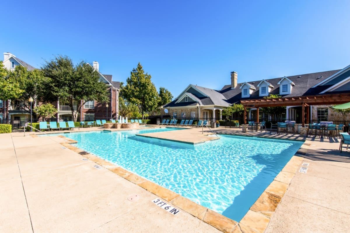 Sparkling pool surrounded by lounge chairs and gazebo area at Marquis at Silver Oaks in Grapevine, Texas