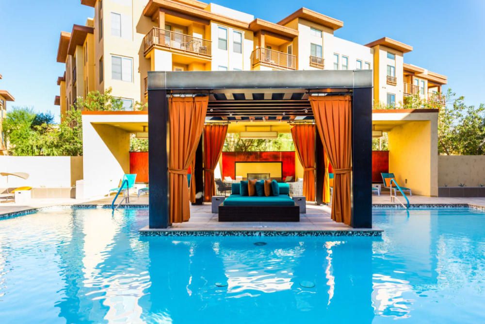 Gazebo with cushioned sofas surrounded by pool and lounge chairs at Marquis at Desert Ridge in Phoenix, Arizona