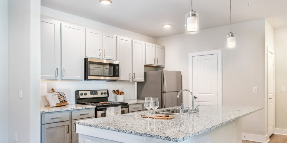Large kitchen with white cabinets and stainless steel appliances at The Mason in Ladson, South Carolina