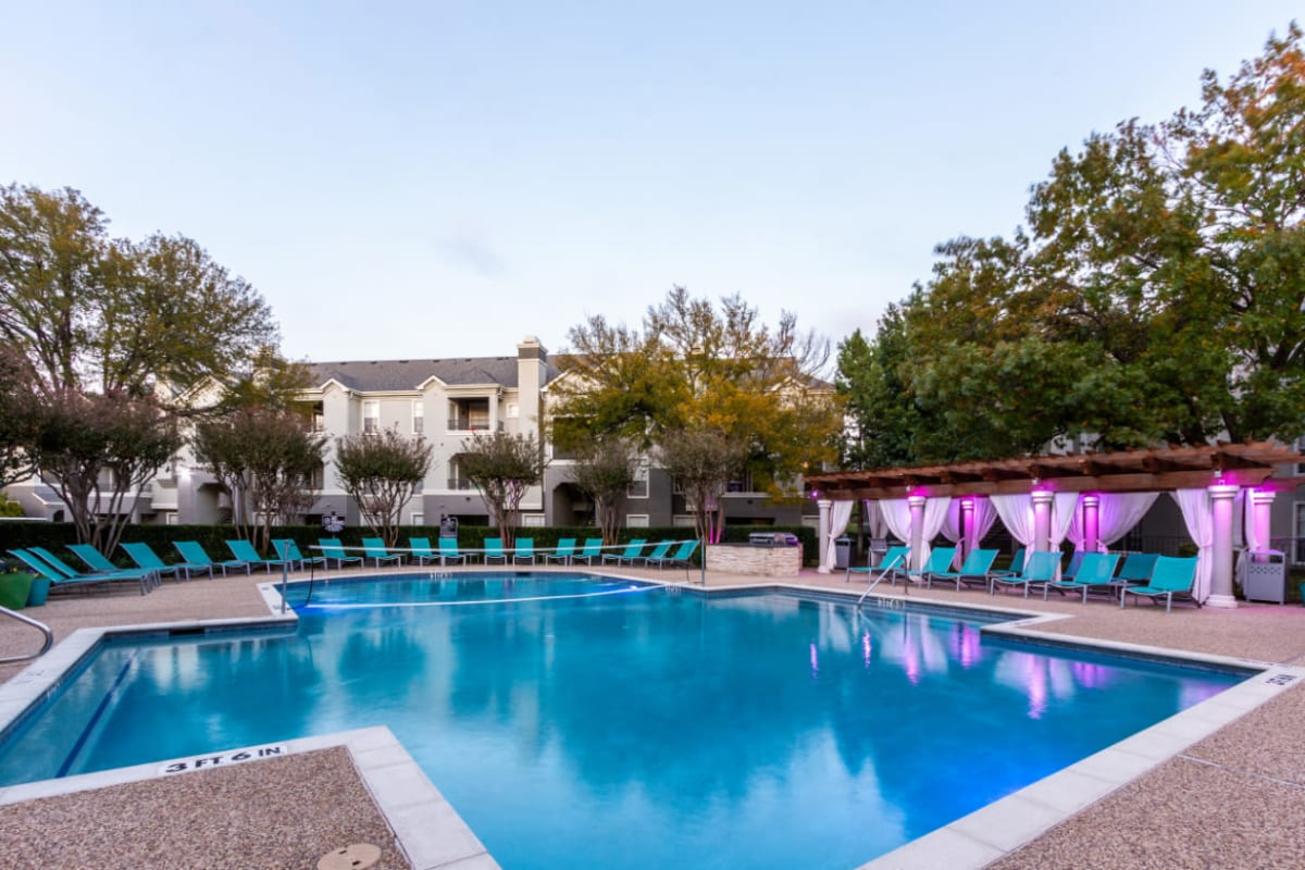 Pool with volleyball net, lounge chairs, and colorful lights under gazebo at sunset at Marquis at Stonegate in Fort Worth, Texas