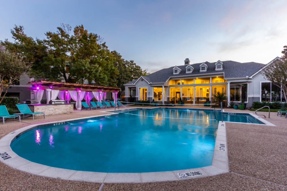 Pool with volleyball net, clubhouse, and colorful lights lounge area at sunset at Marquis at Stonegate in Fort Worth, Texas