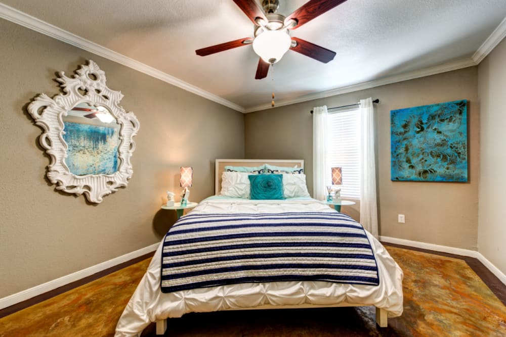 Spacious bedroom with large bed, colorful décor, and ceiling fan at Austin Midtown in Austin, Texas