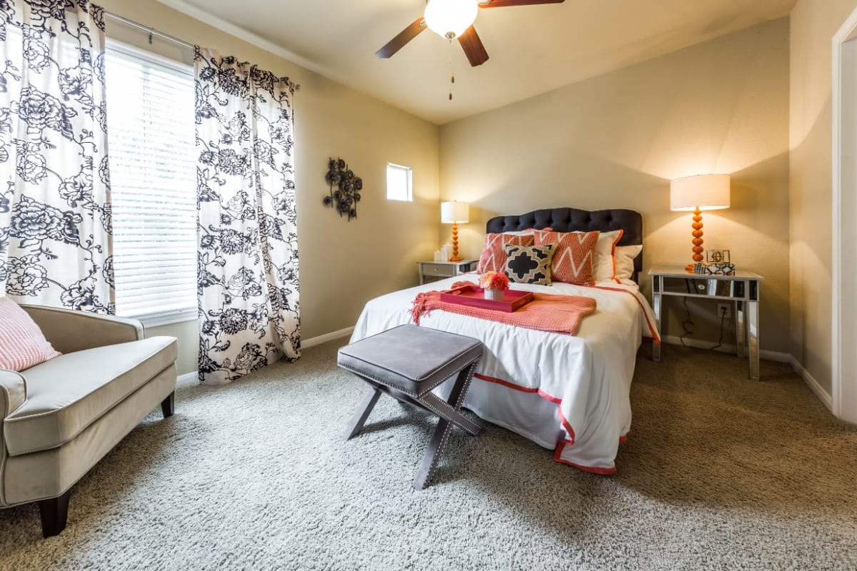 Cozy bedroom with carpet and large window at Marquis at Stonegate in Fort Worth, Texas