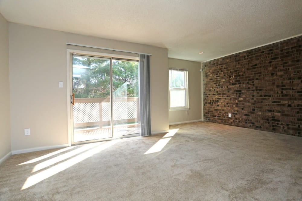 Large living room opening onto private balcony at Laurel Pines Apartments in Richmond, Virginia