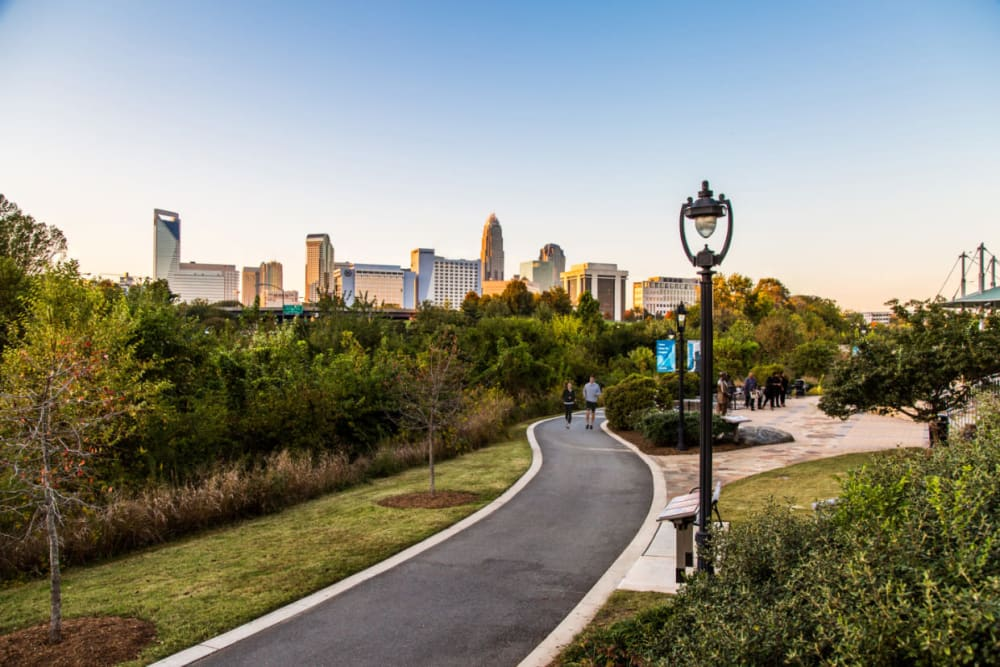 Couple running on paved path through park area at sunset near Marq Midtown 205 in Charlotte, North Carolina