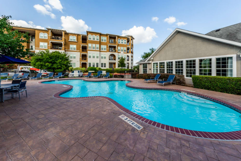 Shallow end of pool surrounded by lounge chairs and dining tables overlooking clubhouse at Marquis at Stone Oak in San Antonio, Texas