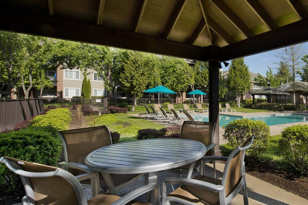 Covered lounge seating by the pool at Cortland Village Apartment Homes in Hillsboro, Oregon