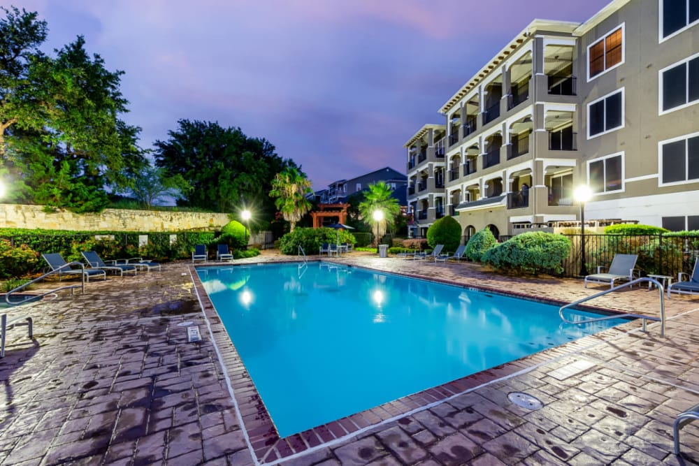 Lighted pool at sunset overlooking units at Marquis at Stone Oak in San Antonio, Texas