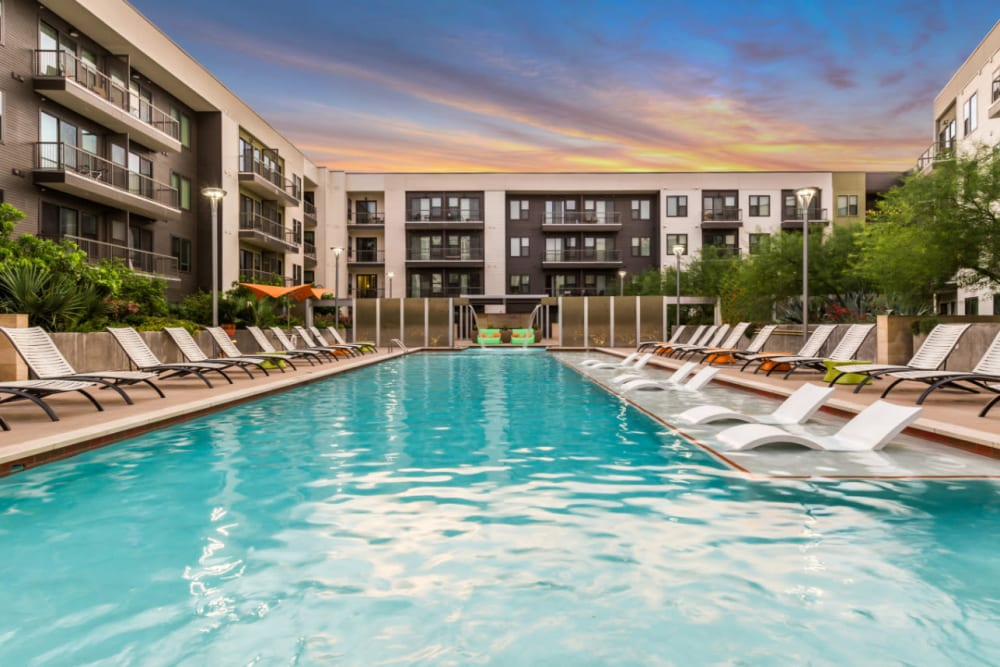 Sparkling resort style pool with lounge chairs at sunset at Marq Uptown in Austin, Texas