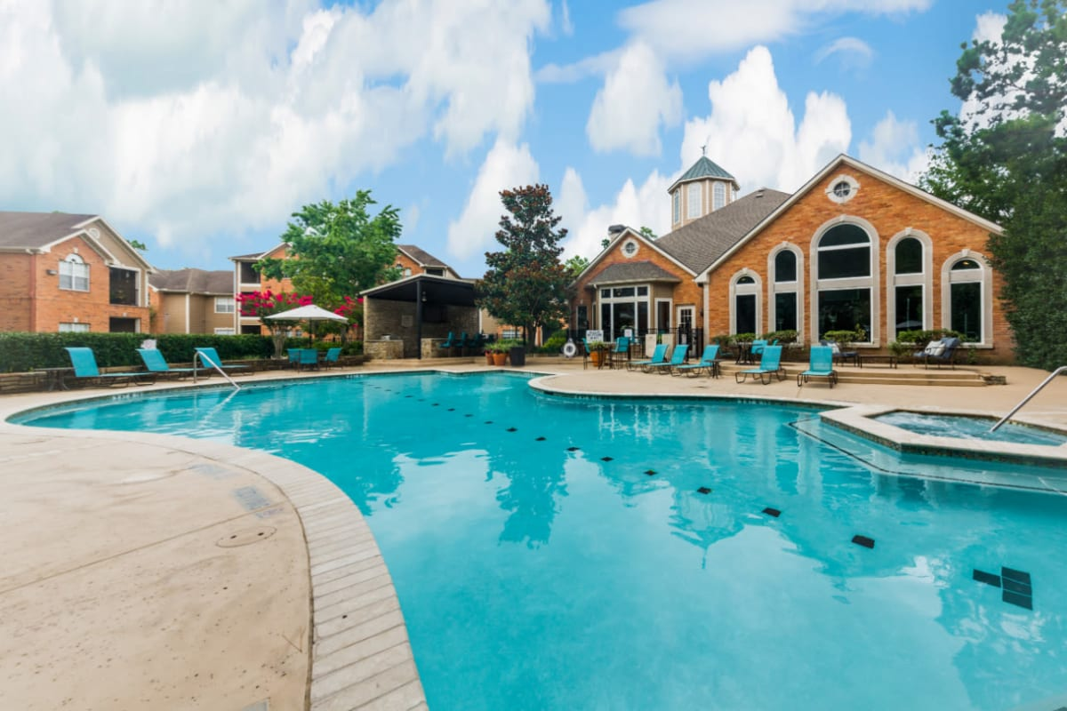 Sparkling pool with hot tub and turquoise lounge chairs at Marquis at Kingwood in Kingwood, Texas