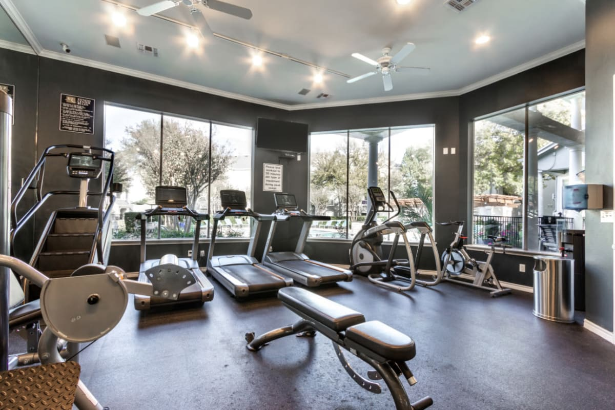 Cardio machines with large windows towards pool at Marquis at Stonegate in Fort Worth, Texas