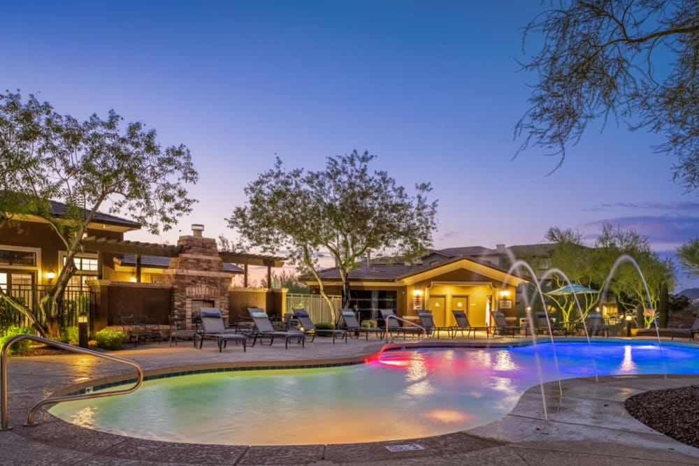Colorfully lighted pool with water features at sunset at Marquis at Sonoran Preserve in Phoenix, Arizona