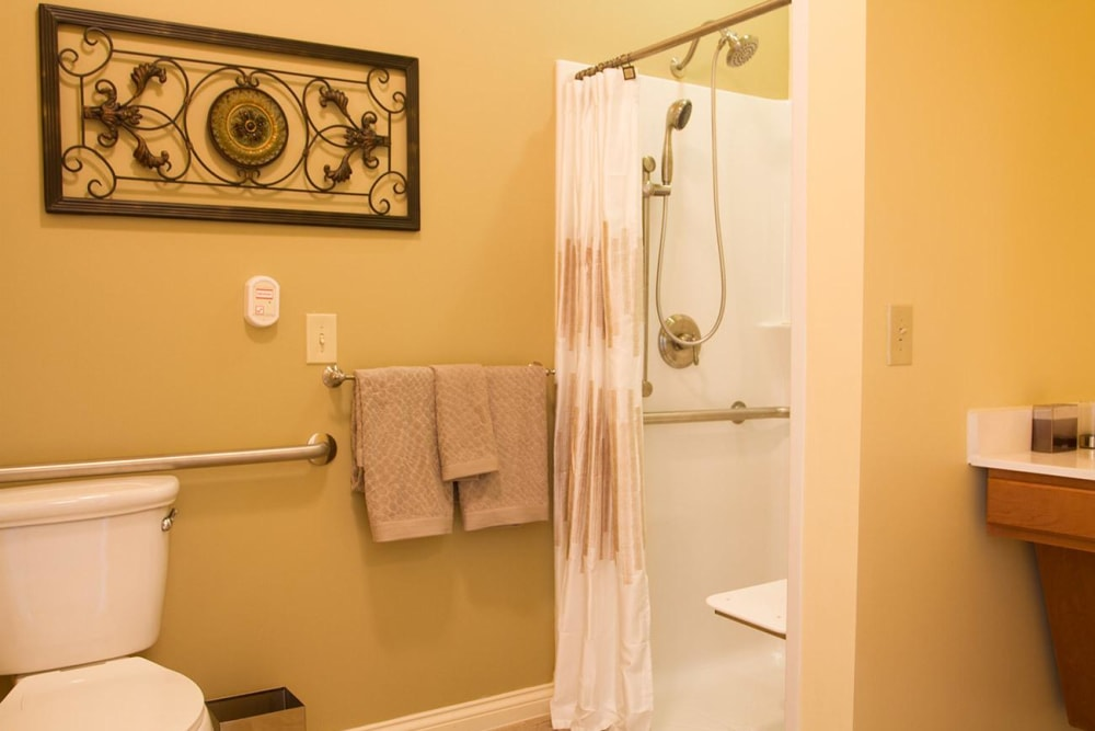 Bathroom with a standing shower and hand rails at Randall Residence of Tipp City in Tipp City, Ohio