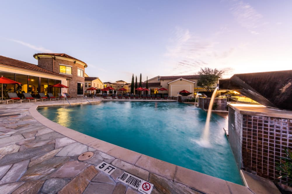 Sparkling pool with waterfall feature at Marquis at the Reserve in Katy, Texas
