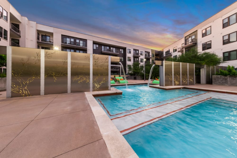 Water feature at end of pool at sunset at Marq Uptown in Austin, Texas