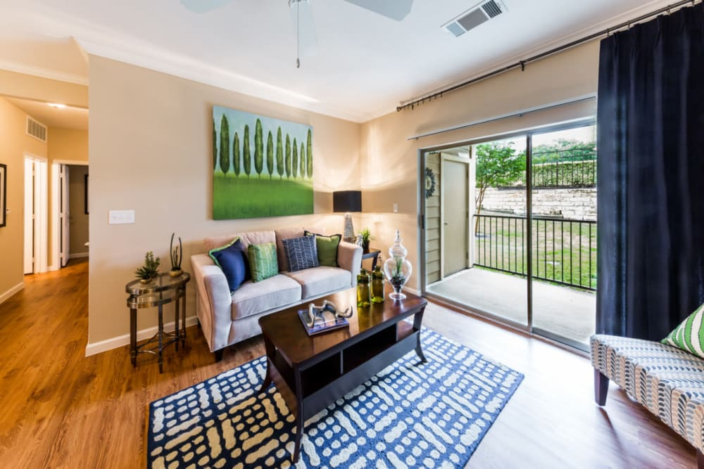 Well-decorated living room with private balcony at Marquis at Canyon Ridge in Austin, Texas