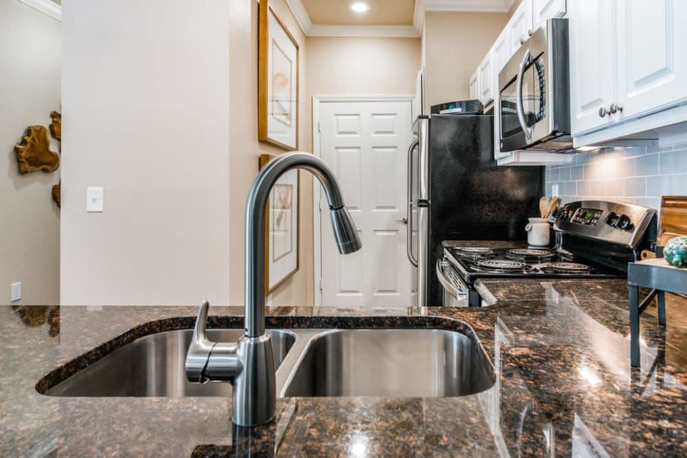Kitchen sink looking towards kitchen with granite counters at Marquis at Carmel Commons in Charlotte, North Carolina