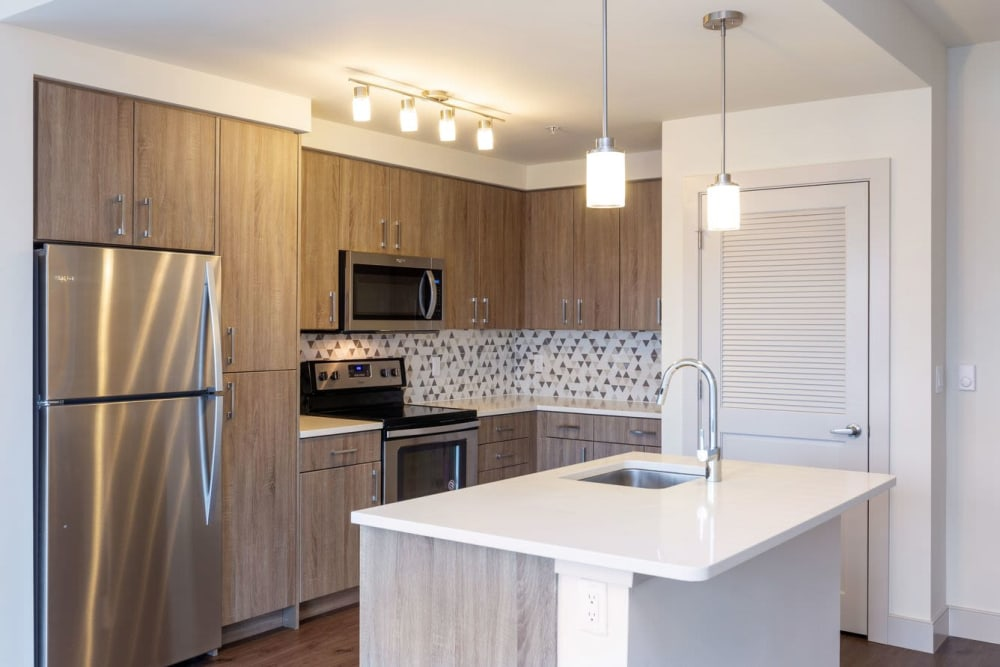 Quartz countertops and stainless-steel appliances in a model apartment's kitchen at ArLo Apartments in Portland, Oregon
