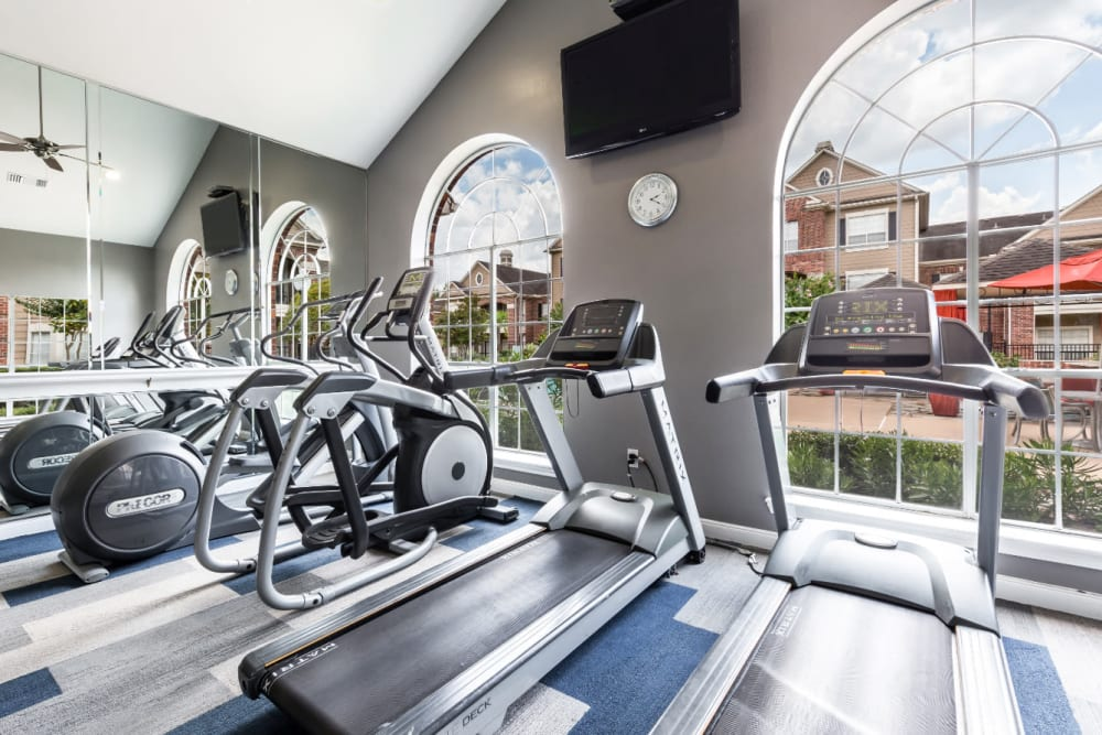 Treadmills and elliptical machine facing large monitor on wall and pool deck at Marquis on Park Row in Houston, Texas