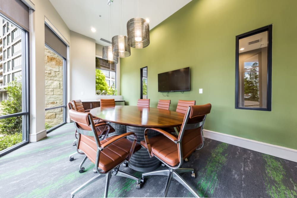 Private business meeting room with television monitor and large windows at Marq Uptown in Austin, Texas