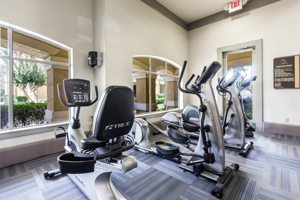 Exercise bike and elliptical machines in fitness room at Marquis at Clear Lake in Webster, Texas