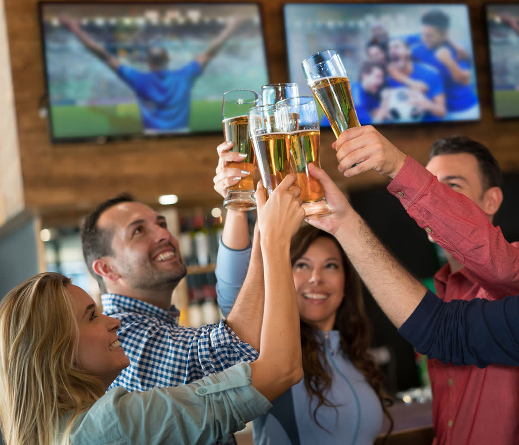 People doing cheers at a restaurant near The Atlantic McKinney Ranch