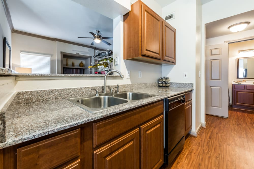 Bright kitchen area with wood cabinets and flooring at Marquis on Park Row in Houston, Texas