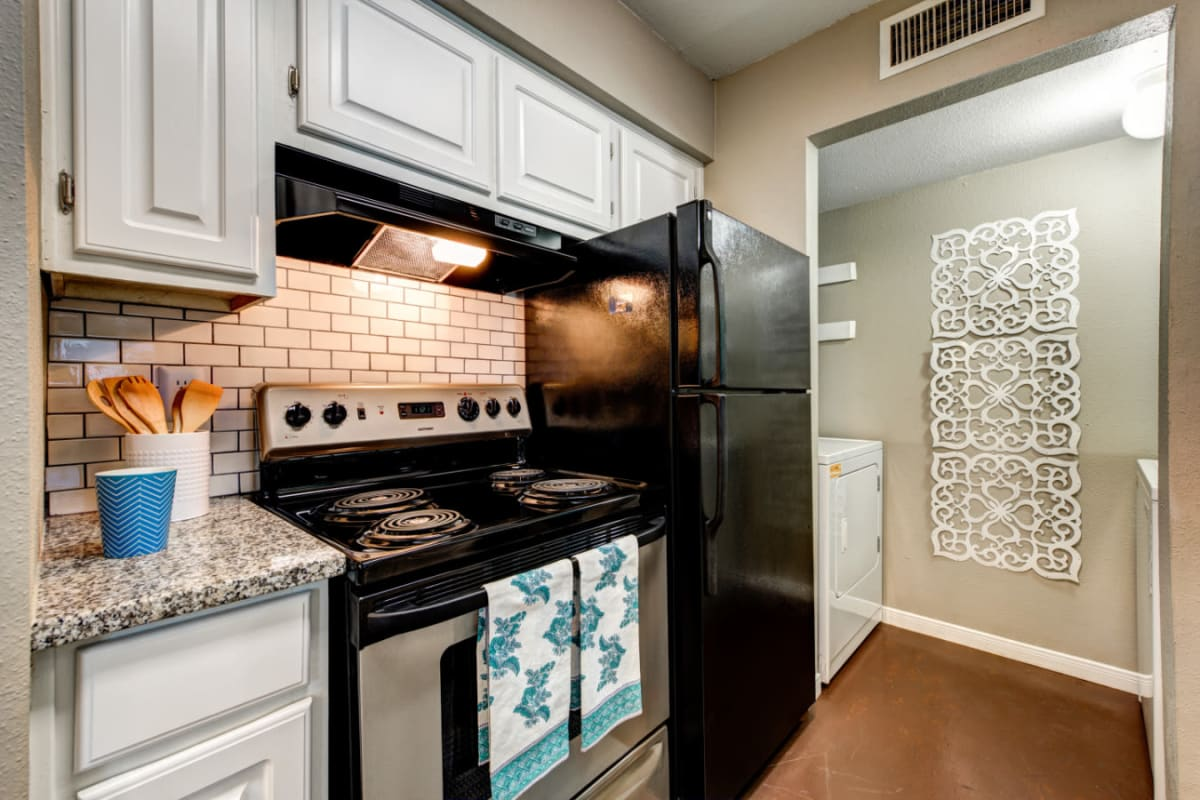 Modern appliances in kitchen with laundry area in background at Austin Midtown in Austin, Texas