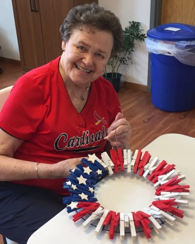 Resident making a wreath look like the American flag at Garden Place Waterloo in Waterloo, Illinois.