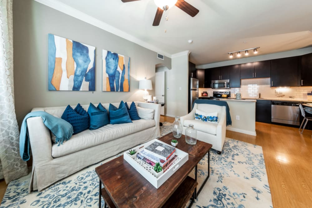 Modern style living room with wood flooring and ceiling fan at Marquis at the Reserve in Katy, Texas