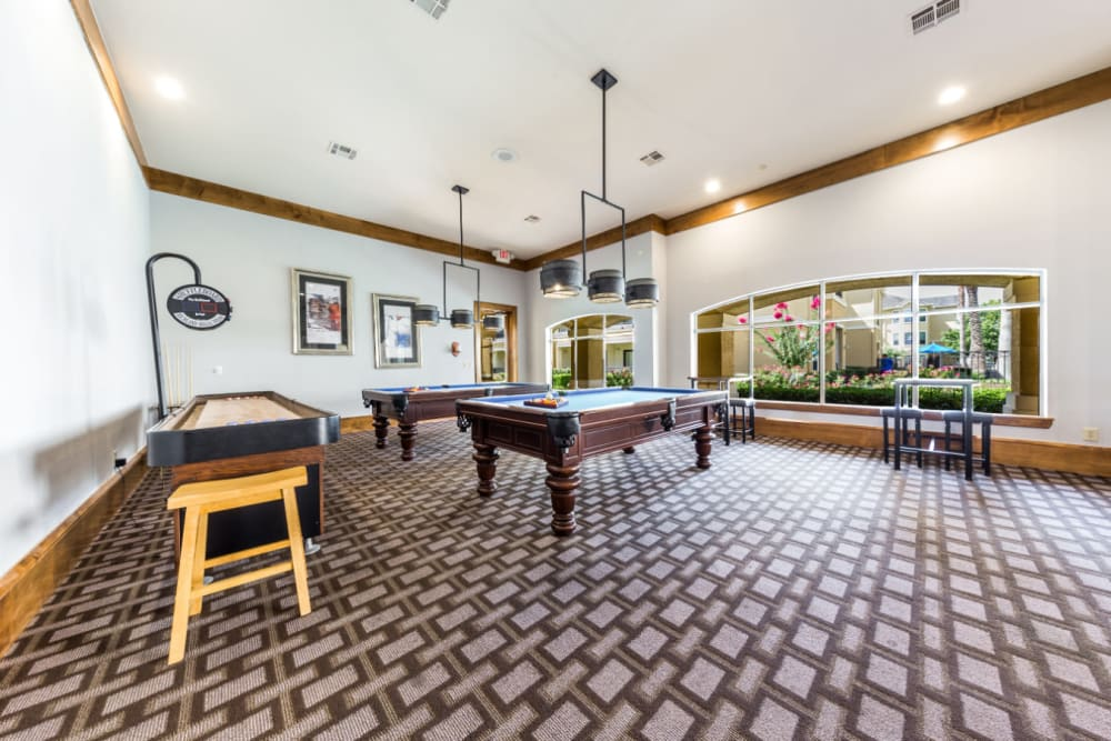 Community clubhouse with pool tables and shuffleboard at Marquis at Clear Lake in Webster, Texas