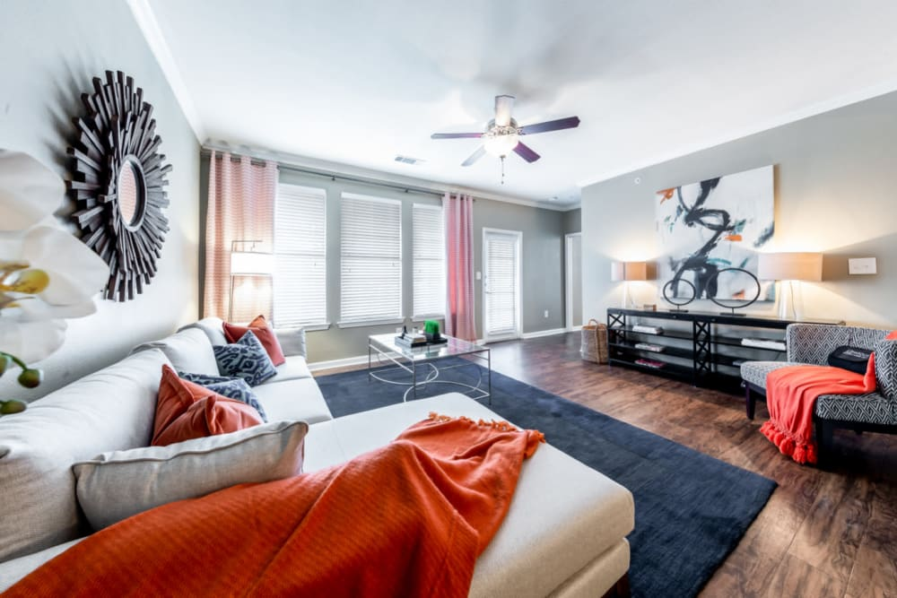 Nicely decorated living room with wood flooring and multiple windows at Marquis at Stone Oak in San Antonio, Texas
