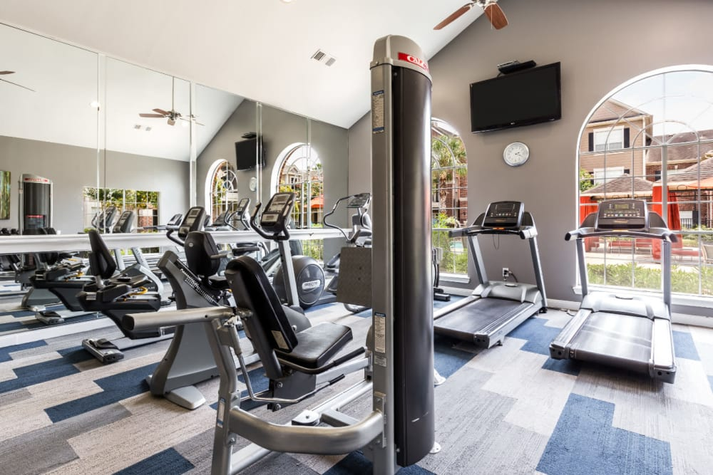 Assisted weight machines and treadmills facing pool deck at Marquis on Park Row in Houston, Texas