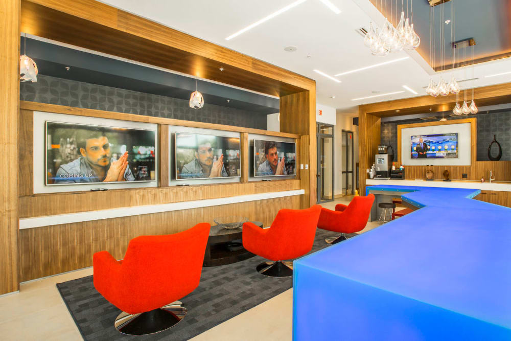 Red chairs lined in front of television screens in lobby area of Marq Midtown 205 in Charlotte, North Carolina
