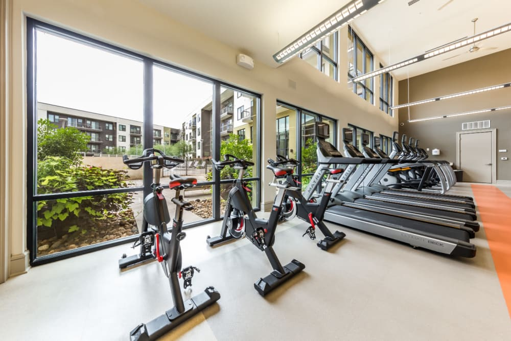 Spin bikes and treadmills facing window in fitness room at Marq Uptown in Austin, Texas