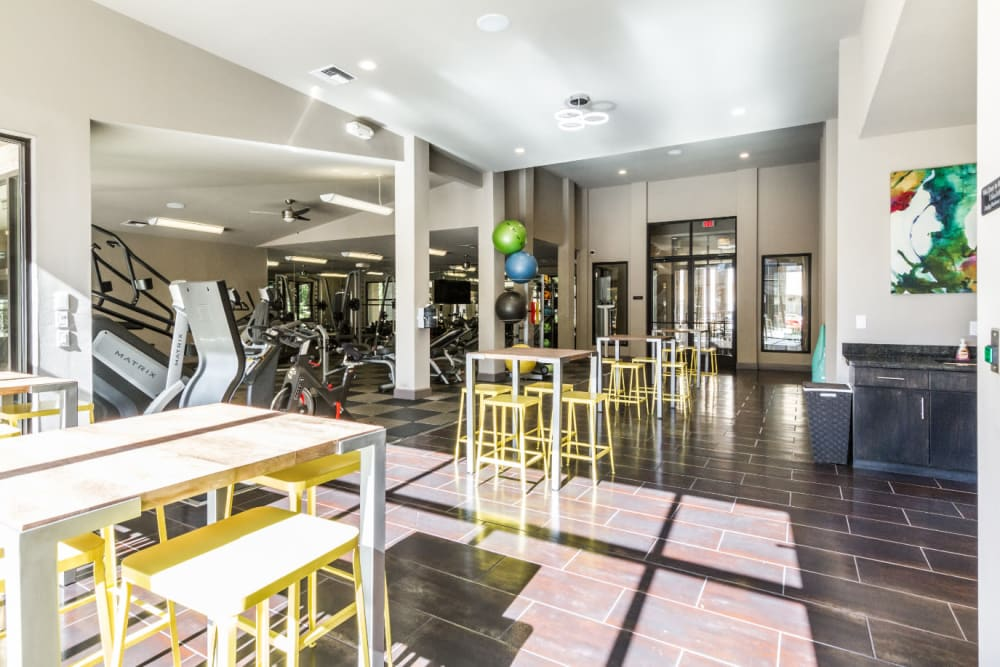 Community kitchen and dining area next to indoor gym at Marquis at Barton Trails in Austin, Texas