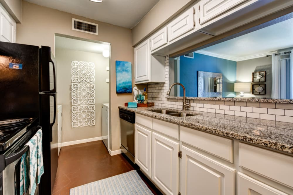 Bright kitchen with granite counter and stainless steel appliances at Austin Midtown in Austin, Texas