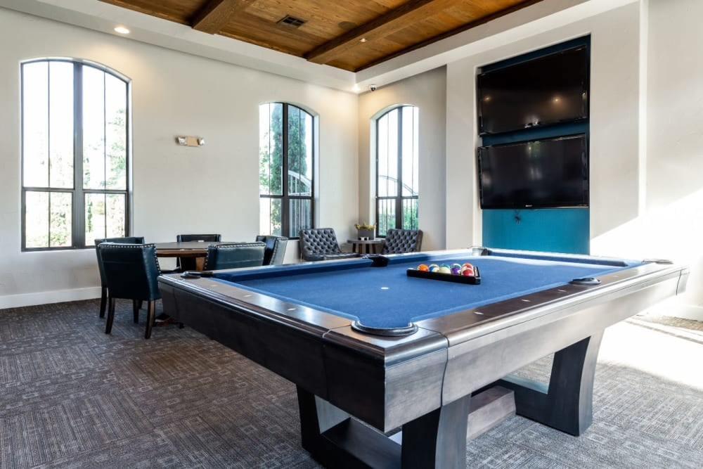 Community clubhouse game room with pool table and large monitors at Marquis at the Reserve in Katy, Texas