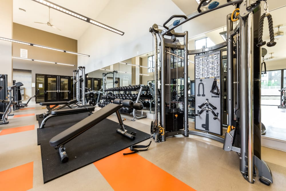 Assisted weight machine and weight benches in fitness room at Marq Uptown in Austin, Texas