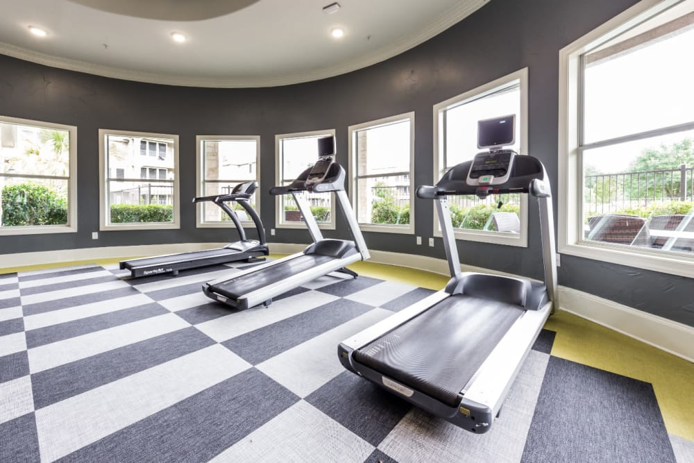 Treadmills with view of the pool in fitness room at Marquis at The Cascades in Tyler, Texas