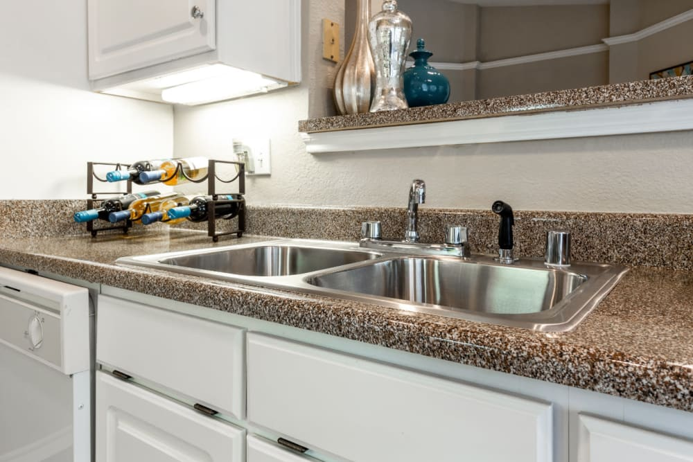 Bright kitchen with laminate counters and white cabinets at Marquis at Waterview in Richardson, Texas