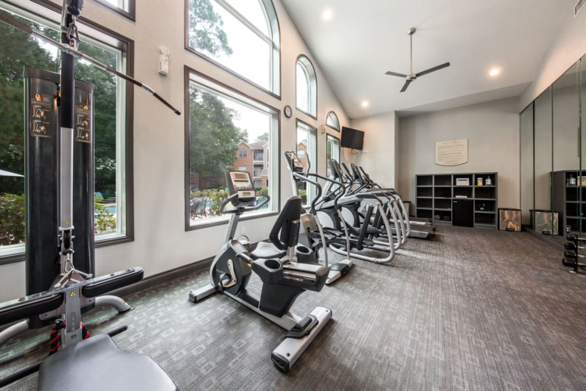 Exercise bikes in fitness room overlooking pool at Marquis at Kingwood in Kingwood, Texas